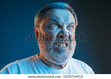 Emotions of a television fan. Screaming, hate, rage. Crying emotional angry man screaming in colorful bright lights at studio. Emotional, mature face. Human, facial expression concept. #1070714912