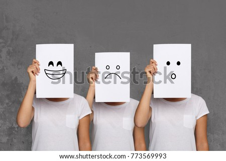 Emotions set. Girl hiding face behind signboard with drawn smileys. Collage of surprised, happy and sad emoticons. #773569993