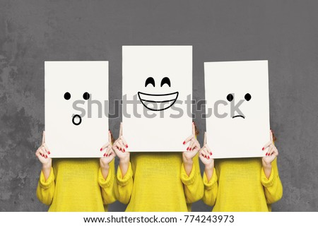 Emotions set. Girl hiding face behind signboard with drawn smileys. Collage of surprised, happy and sad emoticons. #774243973