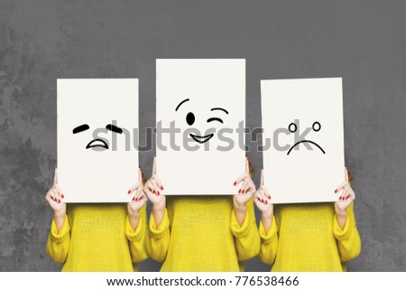 Emotions set. Girl hiding face behind signboard with drawn smileys. Collage of tired, winking and sad emoticons. #776538466