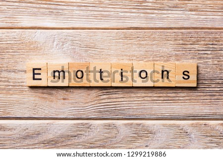 EMOTIONS word written on wood block. EMOTIONS text on wooden table for your desing, concept. #1299219886