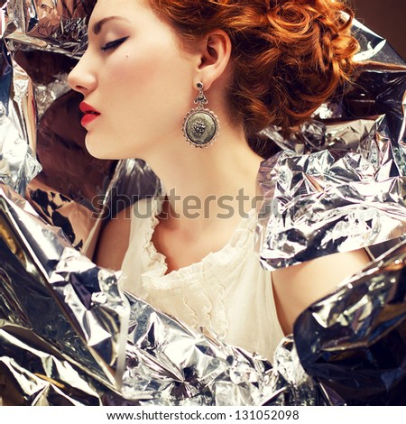 Emotive arty portrait of a fashionable queen-like young woman in white vintage dress posing over wrinkled foil background. Perfect retro hairdo. Close up. Profile. Studio shot