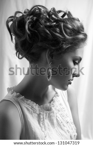 Emotive arty portrait of fashionable queen-like young woman in white vintage dress posing over white curtain background. Perfect retro hairdo. Close up. Profile. Black & white (monochrome) studio shot