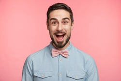 Emotive bearded man wears formal shirt and bow tie, happy to celebrate anniversary, invites friends on party, glad to recieve presents. Happy young unshaven male in festive clothes has good mood