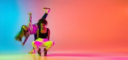 Emotive dance style. Portrait of two young beautiful hip-hop grils dancing on colorful gradient blue orange background in neon. Youth culture, movement, active lifestyle, action, street dance, ad