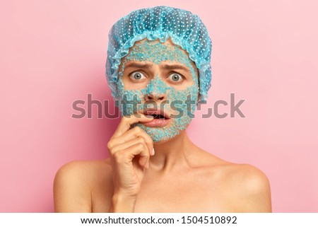 Emotive dissatisfied woman looks with unhappy expression, keeps fore finger on lips, hears bad news from beautician, applies nourishing blue sea salt mask, wears waterproof headgear, poses topless