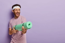 Emotive handsome man pretends shooting in someone with fitness mat, screams loudly, has fun after yoga training, dressed casually, isolated over purple wall with blank space for your advertisement
