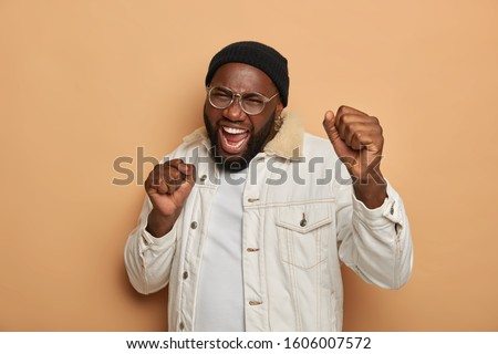 Emotive joyful black man dances with clenched fists, opens mouth widely, expresses positive emotions, poses over beige background, wears black hat and white warm jacket, moves to favourite music Foto stock ©
