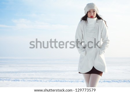 Emotive portrait of a fashionable model in white coat and beret posing at the winter seaside. Sunny weather. French style. Copy-space. Outdoor shot.