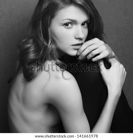 Emotive portrait of a fashionable model with curly hair and natural make-up sitting & posing over gray background. Girl hugs her legs. Perfect skin. Retro style. Black and white studio shot
