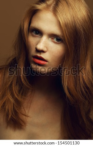 Emotive portrait of a fashionable model with red (ginger) wavy hair and natural make-up. Sexy red lips. Perfect skin with freckles. Retro style. Close up. Studio shot