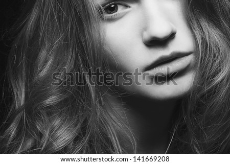 Emotive portrait of a young beautiful girl with curly long hair posing over black background. Perfect skin and hair. Spa salon. Close up. Black and white (monochrome) studio shot