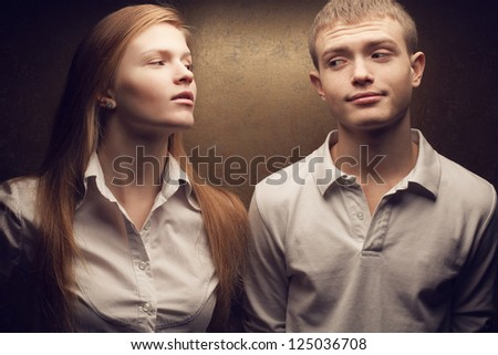 Emotive portrait of gorgeous red-haired fashion twins talking in white shirts posing over golden background together. Studio shot. - stock photo