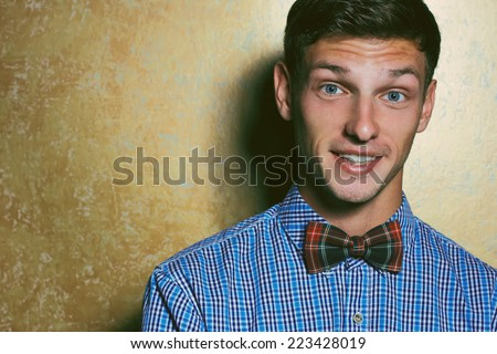 Emotive portrait of smiling handsome young man in blue plaid shirt and Scottish-plaid  bow-tie posing over golden background. White shiny smile and healthy skin. Hipster style. Studio shot. Copy-space