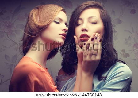 Emotive portrait of two gorgeous girlfriends in blue and orange dresses in a hotel room. Vintage (retro, old hollywood) style. Perfect skin & hair. Close up. Studio shot