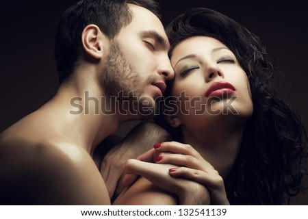 Emotive portrait of two lovers - handsome man and gorgeous woman with perfect hair and skin. Pure passion. Close up. Studio shot