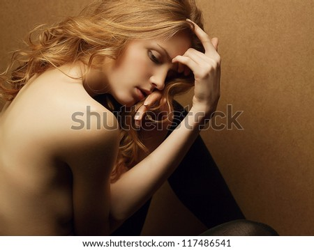 emotive portrait of young beautiful ginger red haired girl on a wooden background. studio shot