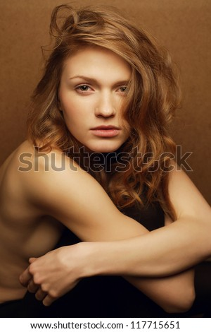 emotive portrait of young beautiful red-haired girl over wooden background. studio shot