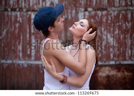 emotive portraite of a stylish couple standing near wooden house. boy holding girl's head. outdoor shot