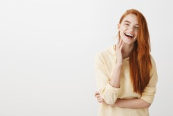 Emotive redhead girl grinning from happiness. Portrait of charming young european female with ginger hair feeling relaxed and joyful while standing with half-crossed hands and laughing over gray wall