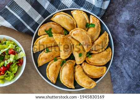 Empanadas - traditional Latin American baked beef pastry on a plate with a fresh salad side dish. Gluten free savory pastries with meat stuffing or filling. Handmade typical dish in Spain or Argentina