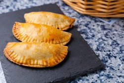 Empanadillas or spanish small pasties on a squared blackboard plate on a kitchen blue granite background with basket. Spanish traditional food and tapas with negative space.