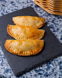 Empanadillas or spanish small pasties on a squared blackboard plate on a kitchen blue granite background with basket. Vertical stills for Spanish traditional food and tapas with negative space.