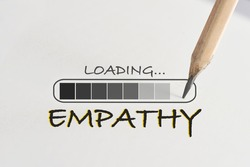 Empathy loading written on white paper with processing symbol and pencil. Understanding concept and learn to listen idea