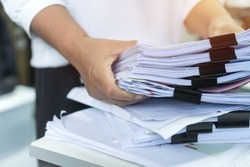 Employee checking business unfinished documents with stacks paper files and managing document achieves preparing meeting planing at busy work in financial office. Tax time in filing information