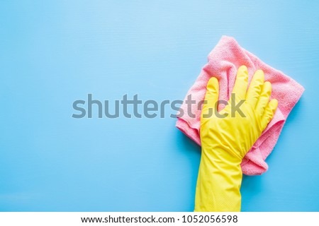 Employee hand in rubber protective glove with microfiber rag wiping blue table, wall or floor surface in room, bathroom, kitchen. Early spring or regular cleanup. Commercial cleaning company concept.