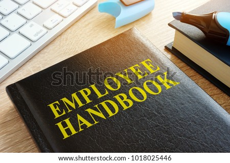 Employee handbook on a wooden desk.