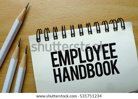 Employee Handbook text written on a notebook with pencils