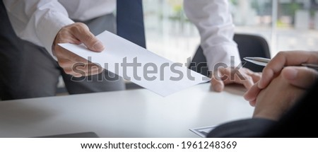 Employee handed over a document envelope and a box of work equipment beside him, Businessman submits resignation documents to their supervisor and take personal equipment in a brown box. Foto stock ©