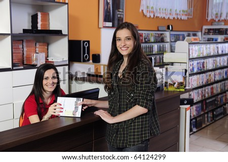 Employee handing over dvd to a costumer at the video rental store