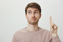 Employee has suggestion. Portrait of handsome european male student raising index finger and looking up with puckered lips, confessing that it was his fault, being embarrassed over gray background