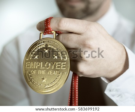 Employee holding golden medal with the text employee of the year. Incentive or motivation concept #583699192