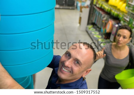 employee in garden center selling pottery to customer or client