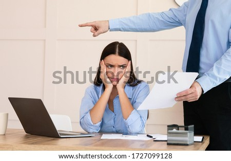 Employee Layoff Dismissal. Boss Firing Woman Worker Showing Employment Agreement Labor Contract Sitting In Modern Office. Cropped Stock photo ©