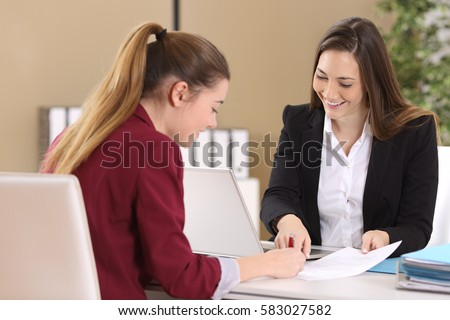 Employee or client and interviewer signing a contract on a desktop in an office interior