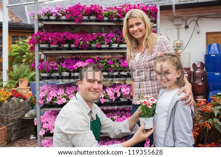 Employee presenting flower pot to little girl with mother in the garden center