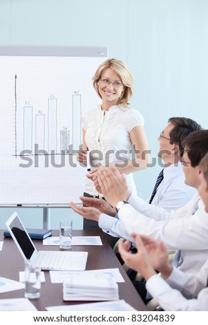 Employees applauding a woman in office