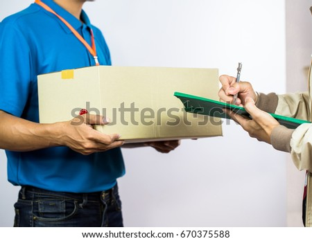 Employees Delivery Man.Postal service - delivery of a package; the postman is giving the package to the customer in front of his house