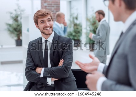 employees discuss their ideas standing in the office lobby