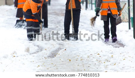 Employees of municipal services in a special form clear the snow from the sidewalk