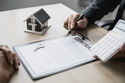 Employees use the calculator to calculate monthly rent for tenants and explain renting details and calculate monthly rent payments to tenants before signing the contract. Renting a house concept.