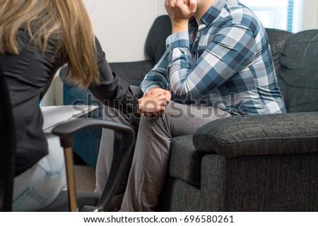 Employer comforting unemployed and not hired male applicant after failed job interview. Therapist or psychiatrist holding sad or depressed patient's hand and giving support.