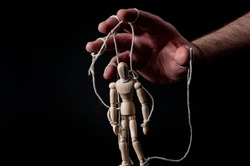 Employer manipulating the employee, emotional manipulation and obey the master concept with ominous hand pulling the strings on a marionette with moody contrast on black background