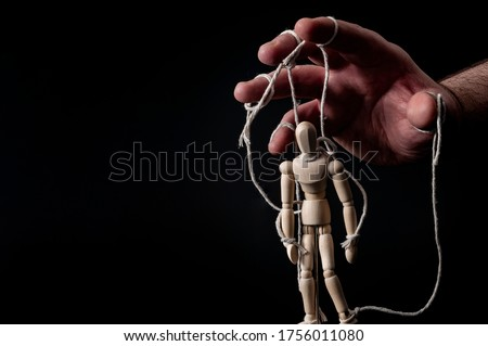 Employer manipulating the employee, emotional manipulation and obey the master concept with ominous hand pulling the strings on a marionette with moody contrast on black background with copy space Foto stock ©