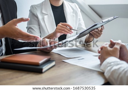 Employer or committee holding reading a resume with talking during about his profile of candidate, employer in suit is conducting a job interview, manager resource employment and recruitment concept. Stock photo ©