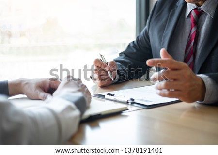 Employer or recruiter holding reading a resume during about colloquy his profile of candidate, employer in suit is conducting a job interview, manager resource employment and recruitment concept. Foto d'archivio ©